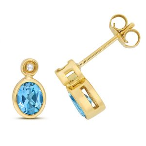 Diamond and Oval Shaped Blue Topaz Stud Earrings in 9ct Yellow Gold