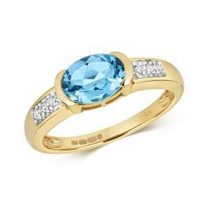 Diamond and Bezel Set Oval Blue Topaz Dress Ring with Diamond Shoulders in 9ct Yellow Gold